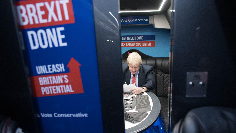 Boris Johnson schreibend an Tisch