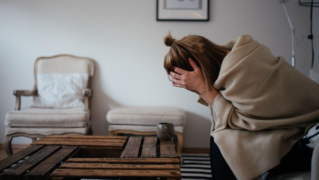 Eine Frau stützt den Kopf in die Hände (Symbolbild)