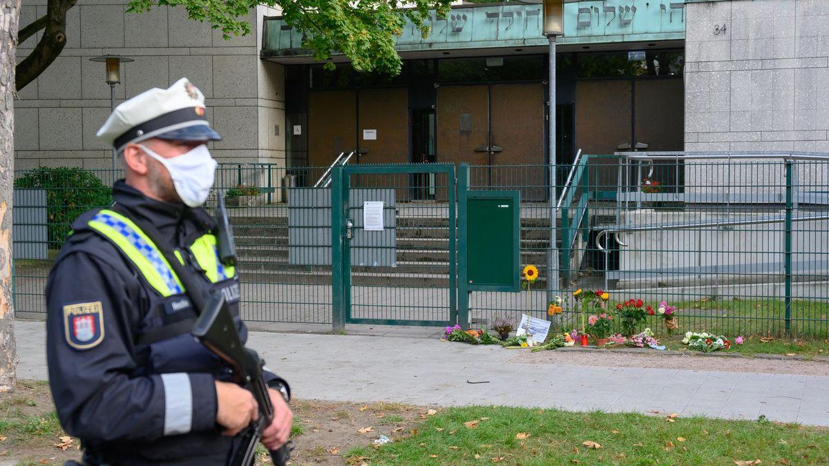 Ein Polizist mit Maschinenpistole patrouilliert am Tatort vor dem Eingang der Synagoge in Hamburg, am Zaun stehen Blumen und Kerzen