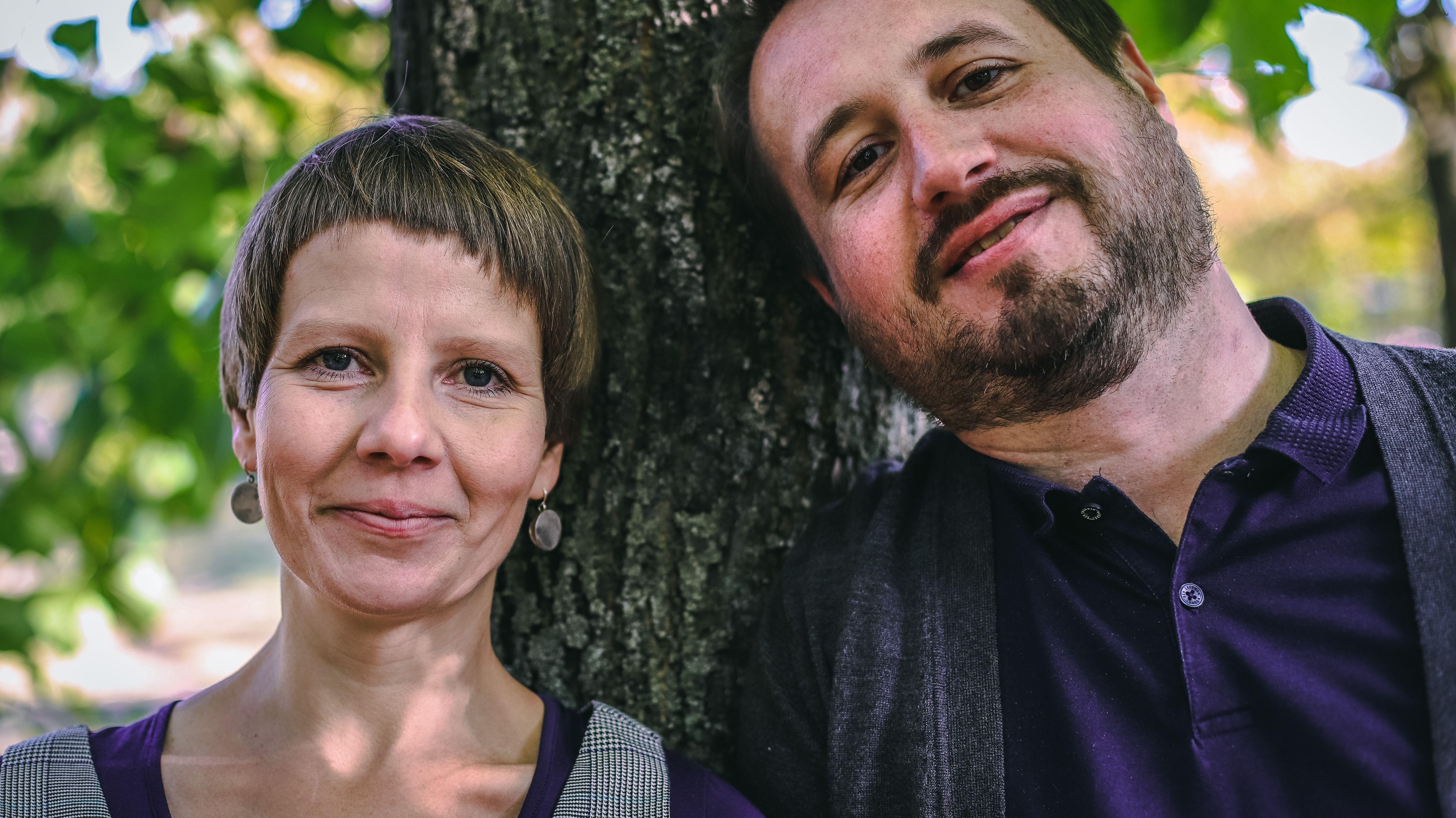 Portraitbild: Die beiden Eltern lehnen an einem Baum