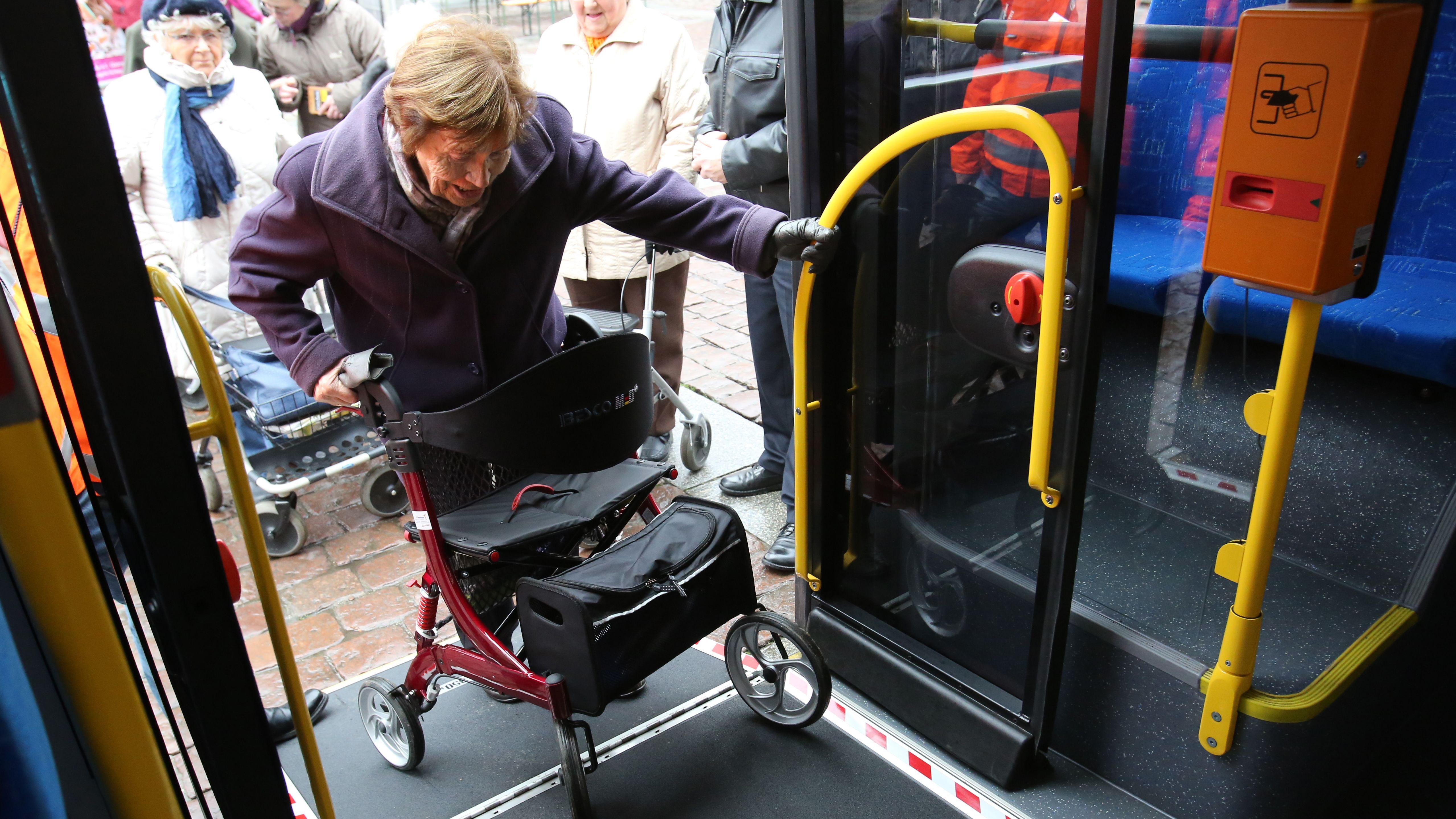 Seniorin mit Rollator steigt in einen Bus ein