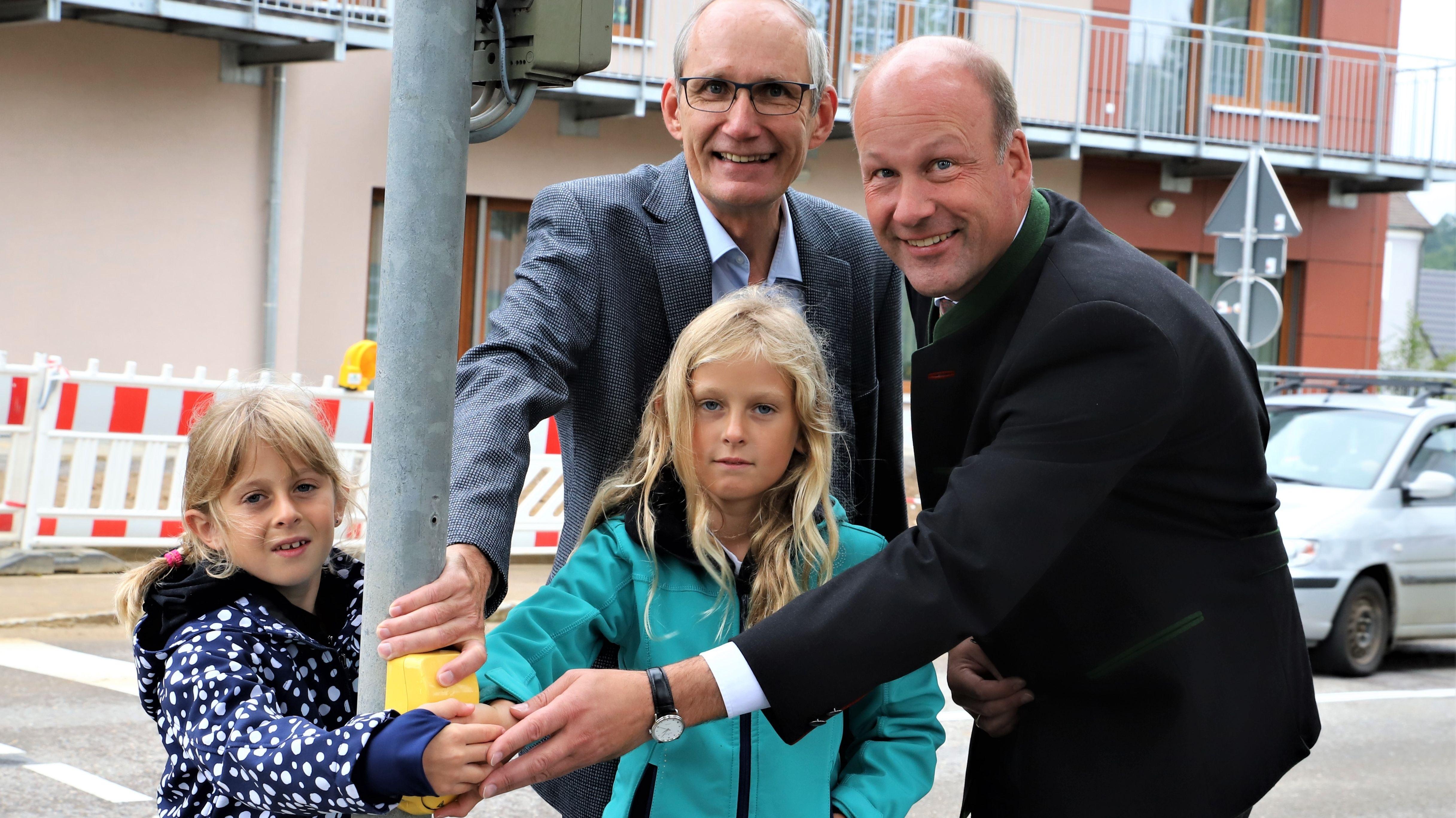 Marie und Katharina Werner, Weldens Bürgermeister Peter Bergmeir und der Augsburger Landrat Martin Sailer an einer Fußgängerampel