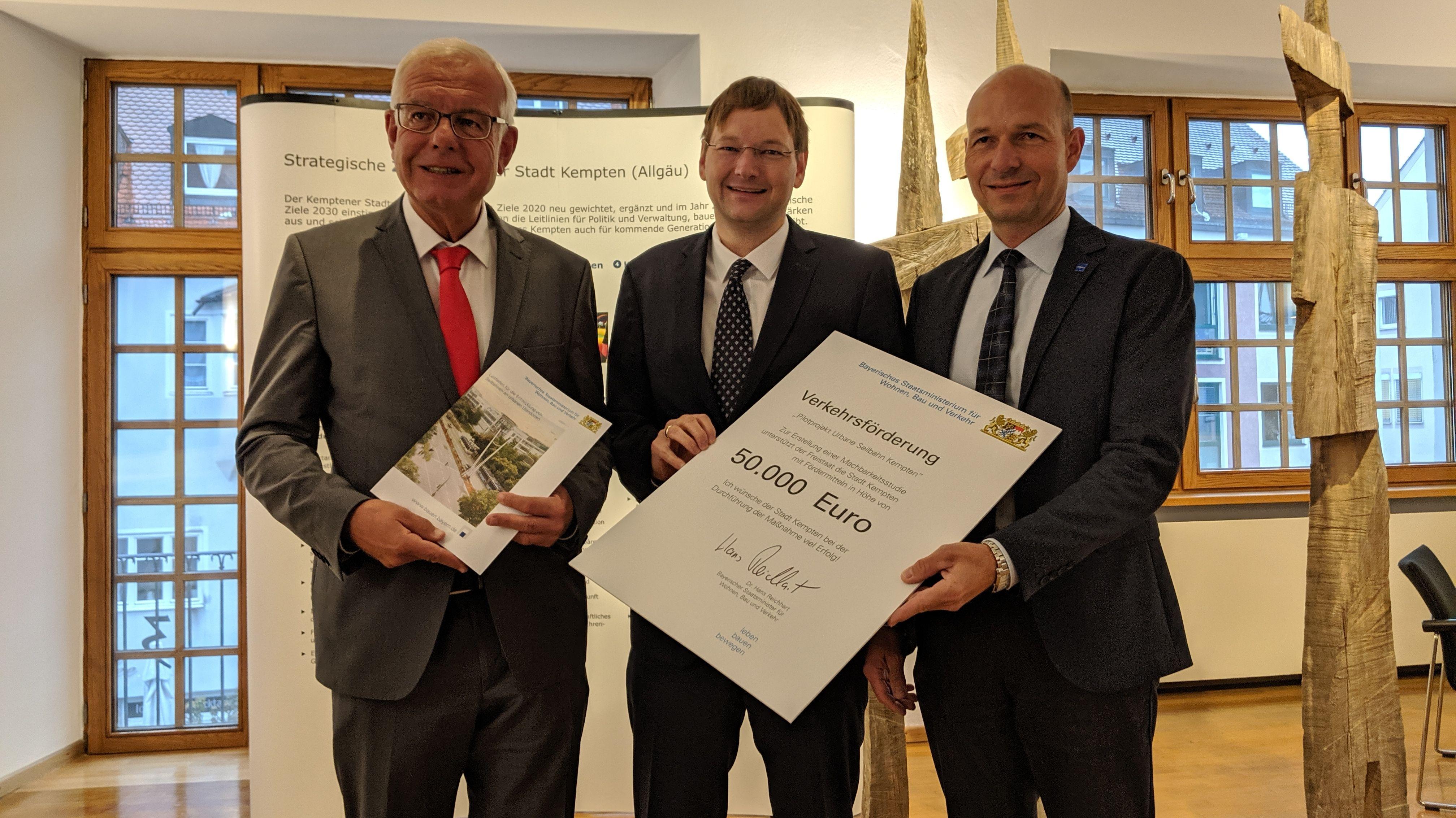 Verkehrsminister Hans Reichhart (Mitte) überreicht den Förderbescheid an Kemptens OB Thomas Kiechle (rechts). Links MdL Thomas Kreuzer (CSU).