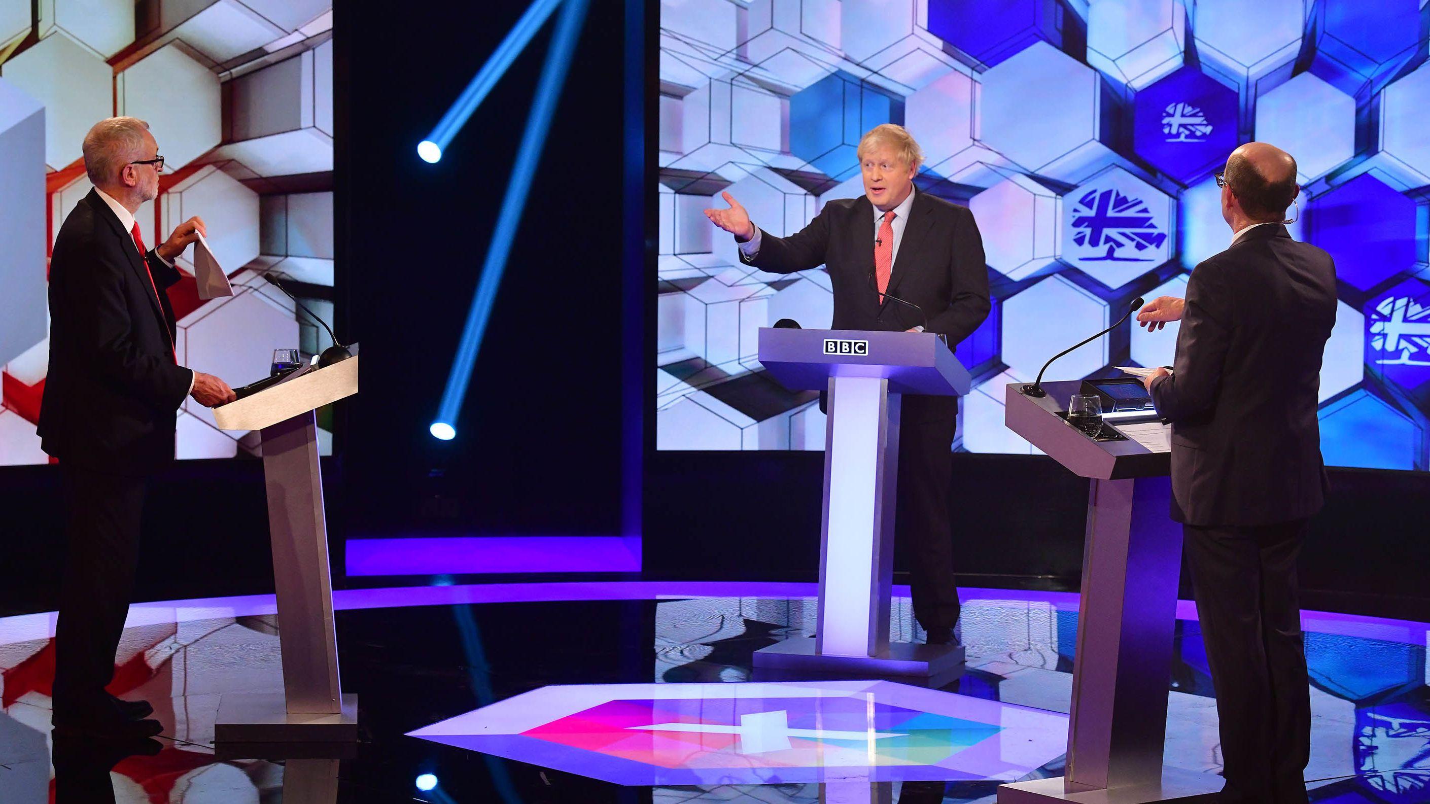 Premierminister  Boris Johnson (mitte) und der Vorsitzende der Labor Party Jeremy Corbyn (links) im Fernsehduell.