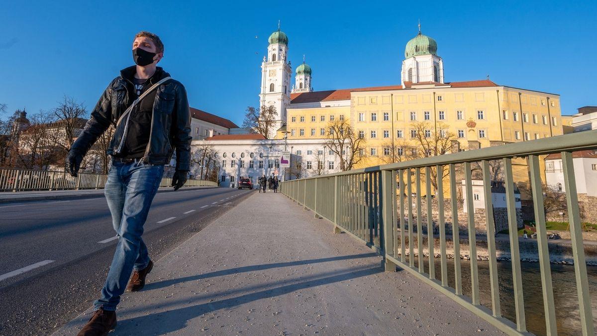 Passau: Ein Mann mit Mund-Nasen-Schutz geht vor dem Dom St. Stephan auf der Innbrücke.