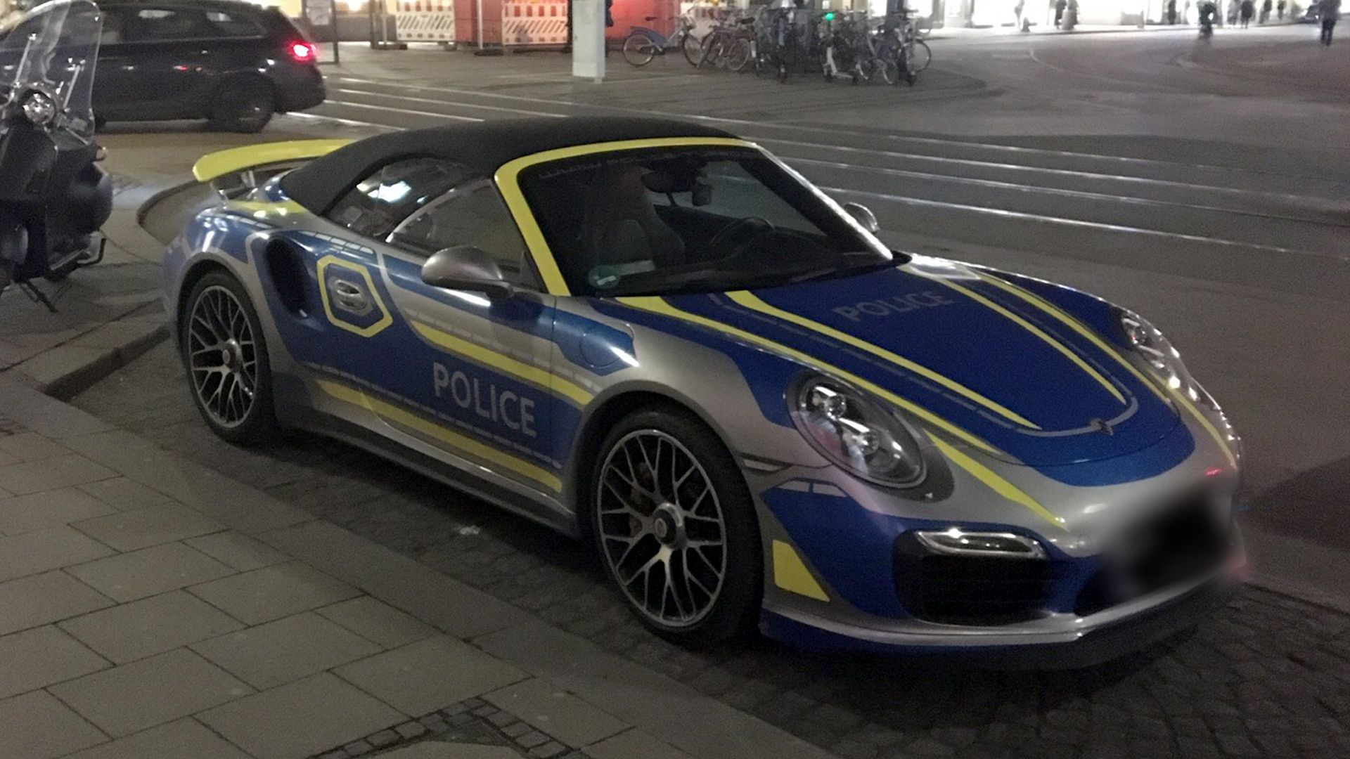 """Blaue Flächen, gelbe Streifen und die Aufschrift """"Police"""" - in München fährt ein falscher Polizei-Porsche durch die Stadt."""