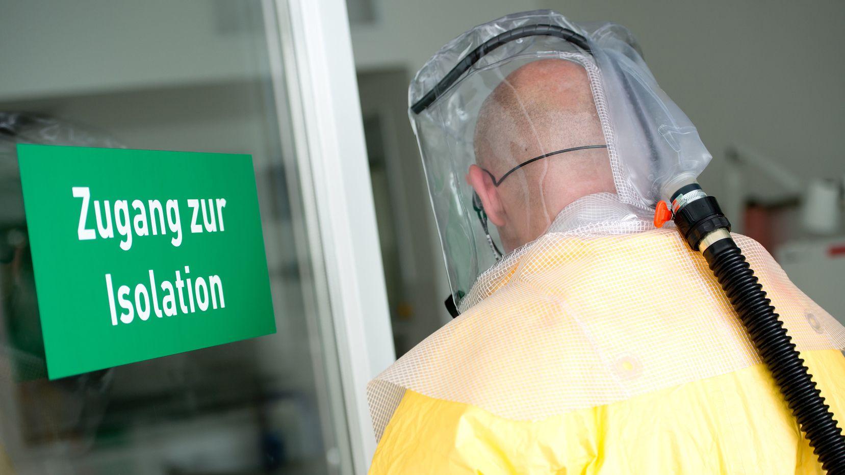 Ein Mann in Schutzausrüstung betritt eine Sonderisolierstation in einem Münchner Klinikum.