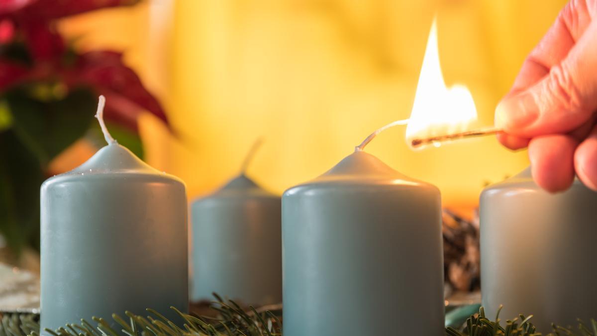 Kerze auf Adventskranz wird angezündet.
