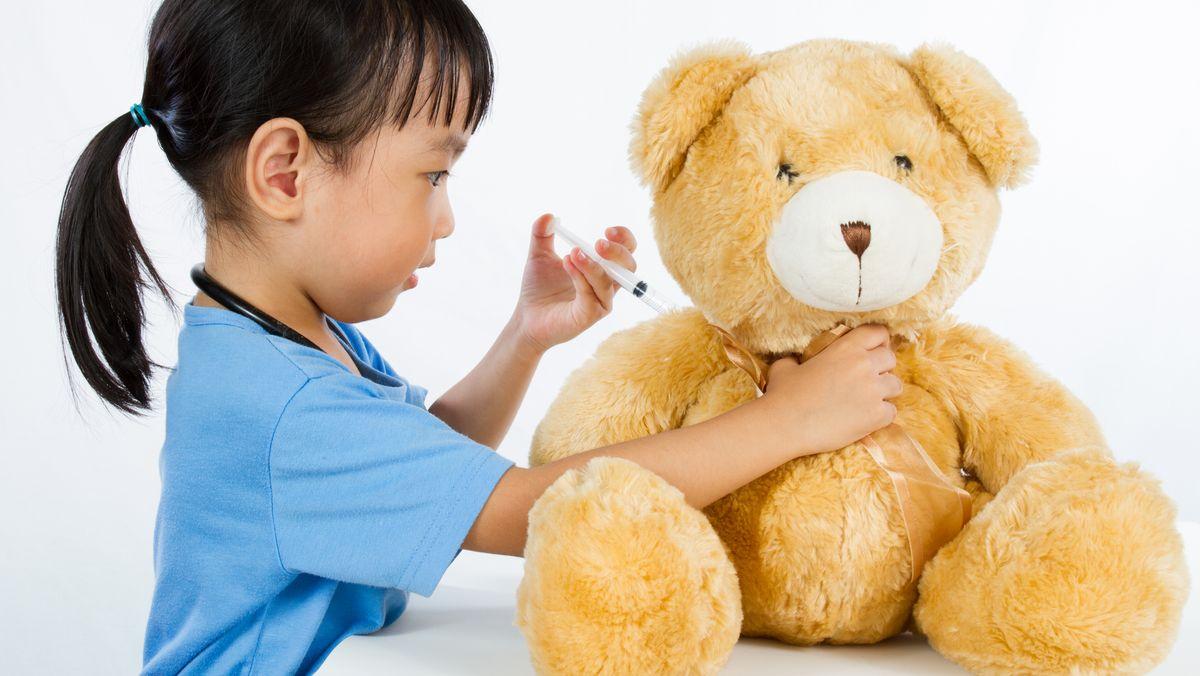 Kind impft einen Teddy.