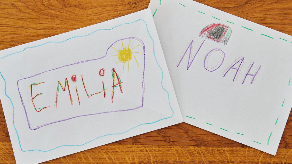 """Blätter mit Aufschriften """"Emilia"""" und """"Noah"""" in Kinderschrift au einem Holztisch"""