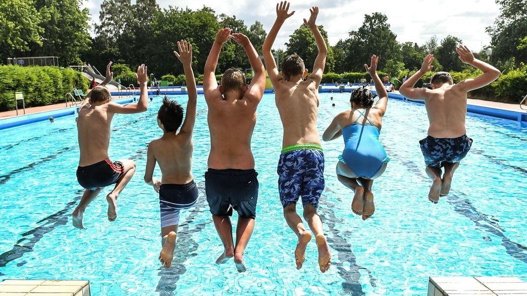 Kinder in einem Freibad springen ins Becken