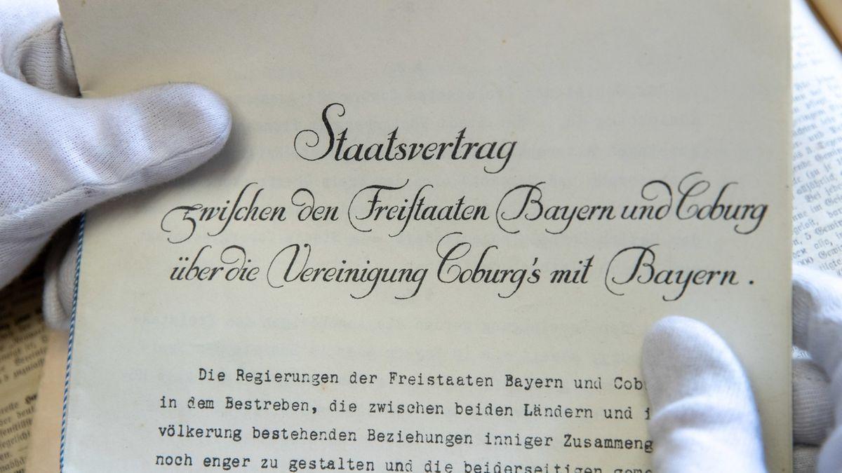 Zwei Hände mit weißen Stoffhandschuhen halten den Staatsvertrag zwischen den Freistaaten Coburg und Bayern