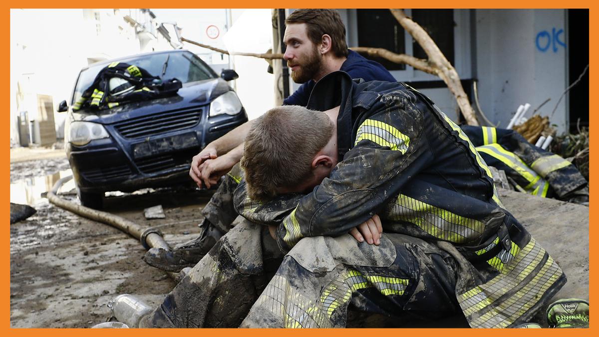 Zwei Feuerwehrmänner sitzen in den Trümmern nach dem Hochwasser im Westen Deutschlands.