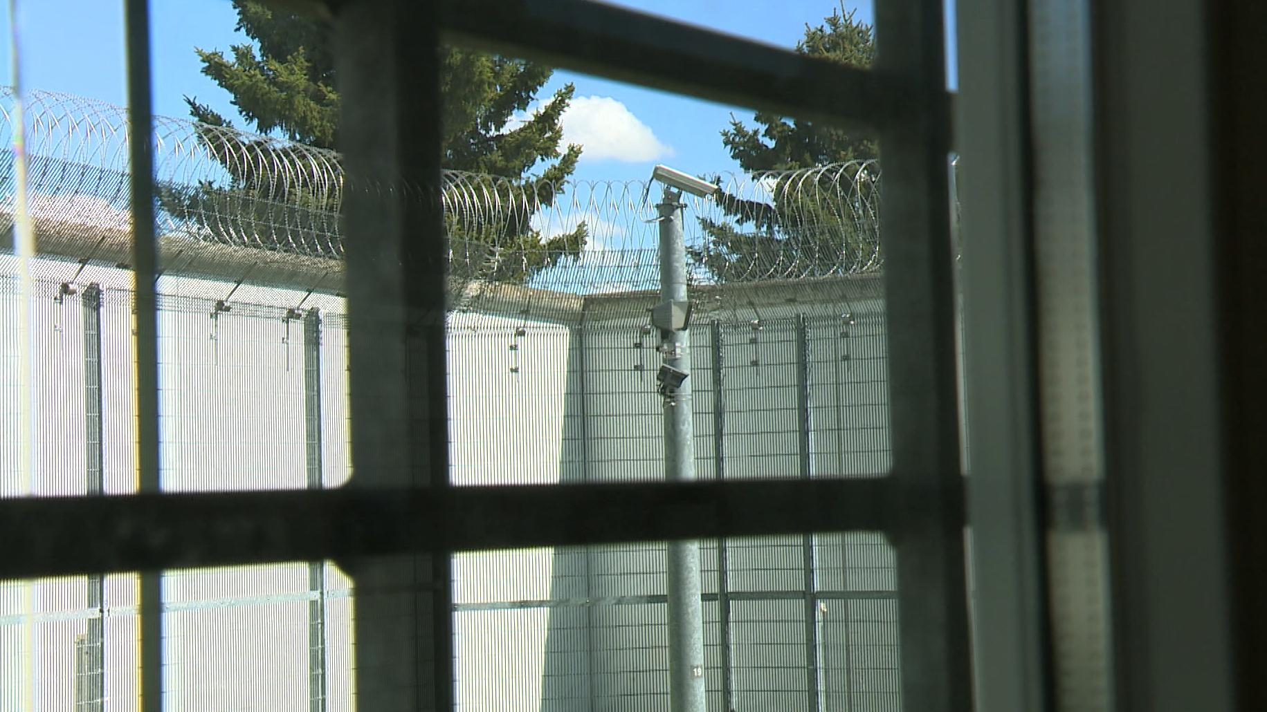 Blick aus einem vergitterten Fenster auf einen Gefängniszaun