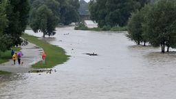 München: Passanten gehen nach Regenfällen am überschwemmten Ufer der Isar entlang. (04.08.2020)   Bild:picture alliance/Peter Kneffel/dpa