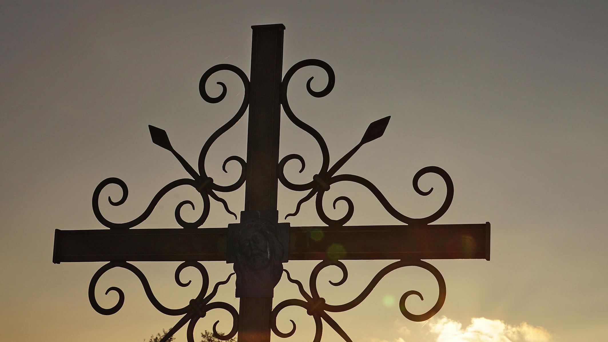 Ein schmiedeeisernes Friedhofskreuz im Sonnenuntergang