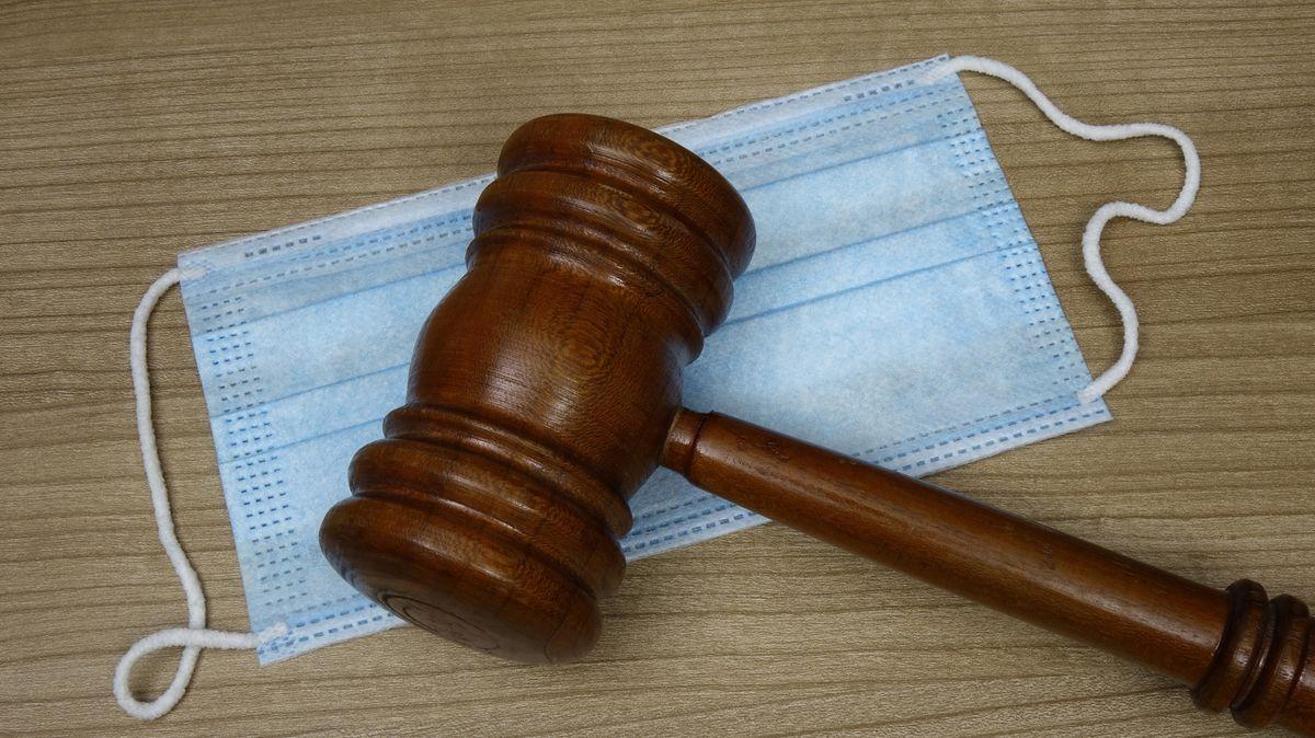 Ein Richterhammer liegt auf einer Mundschutzmaske