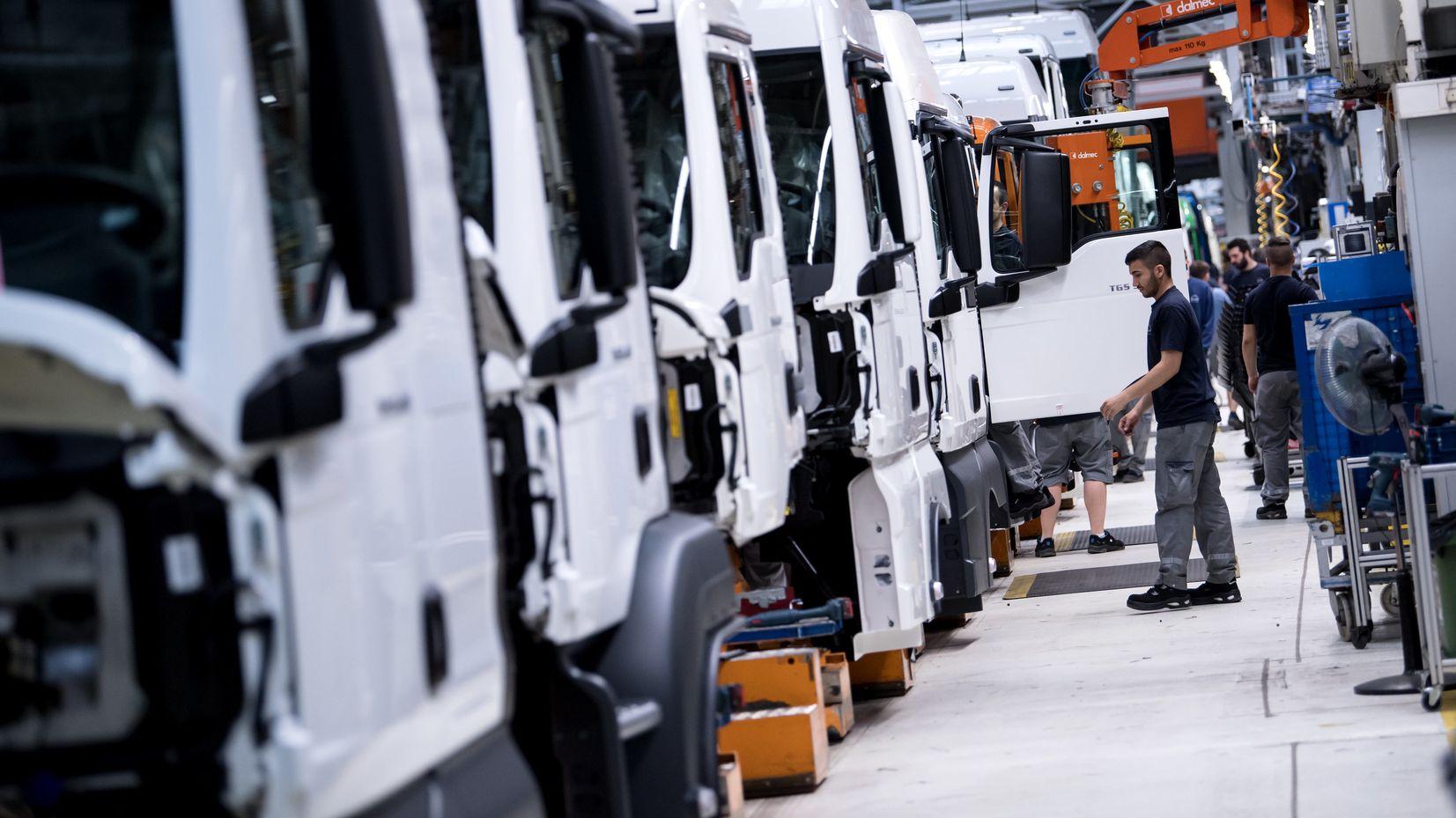 Mitarbeiter von MAN Truck & Bus arbeiten an einer Produktionsstraße an einem LKW