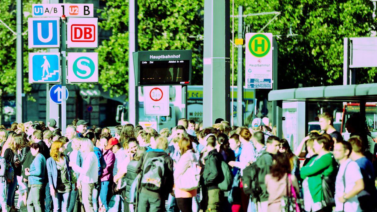 Menschen warten an einer Bushaltestelle.