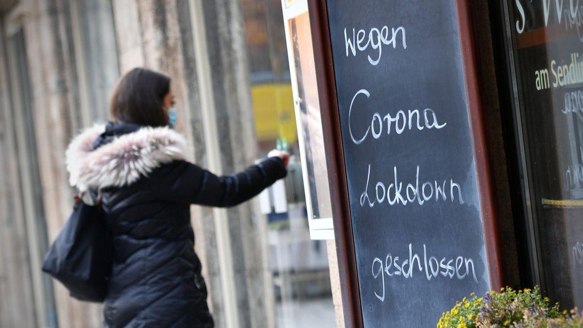 Eine Frau steht vor einem geschlossenen Geschäft (Symbolbild)