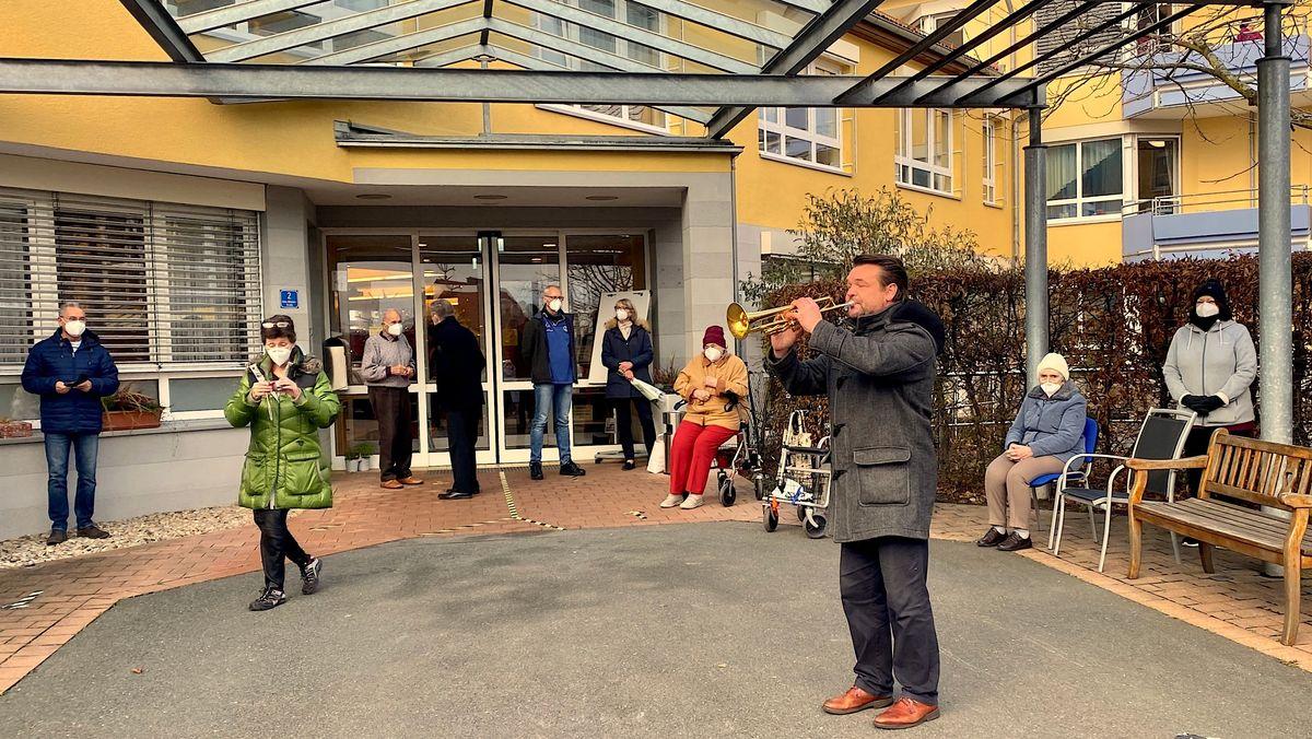 Trompeter Jens Lohmüller spielt vor einem Seniorenheim