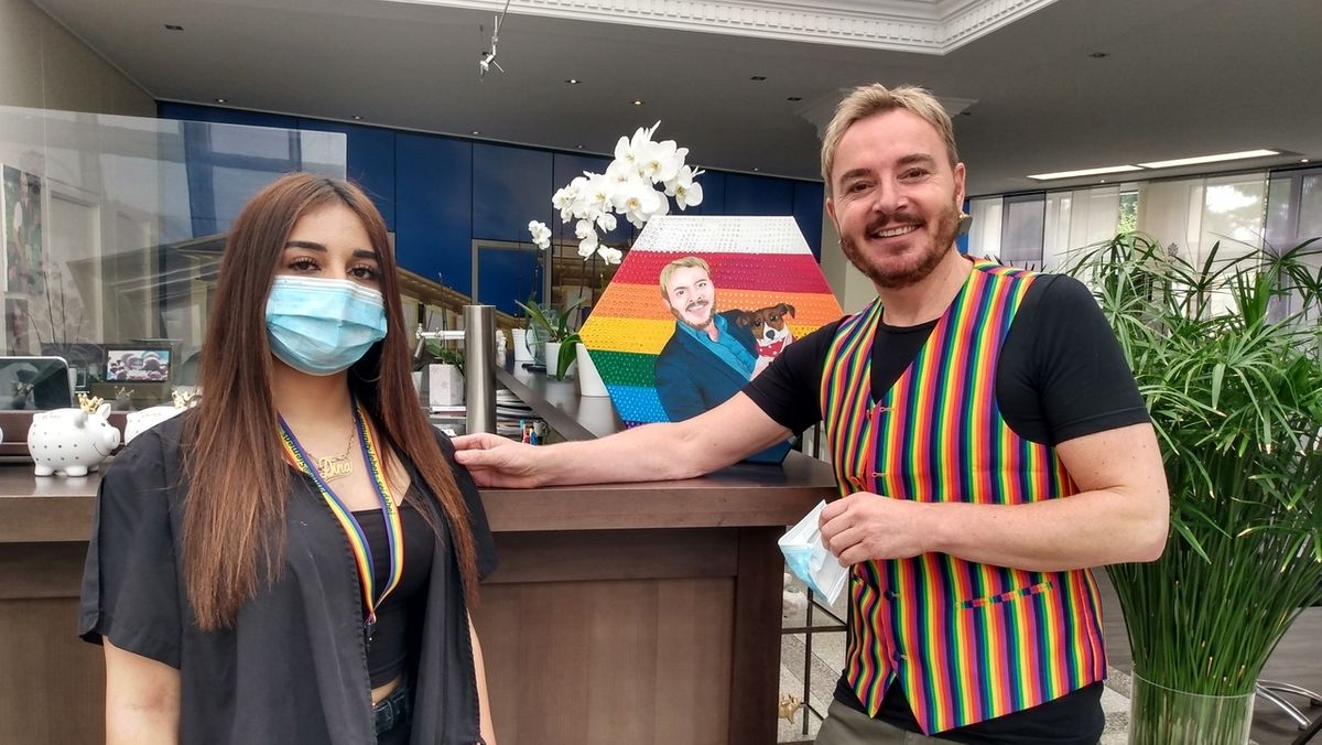 Ein Mann in Regenbogenweste und eine Frau mit Regenbogen-Schlüsselband in einem Friseursalon.