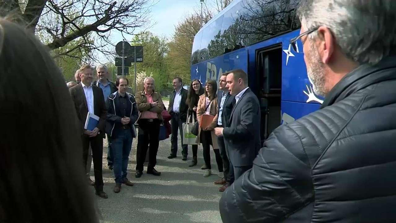 Bürger und Politiker diskutieren vor der Bustour über die Elektrifizierung.
