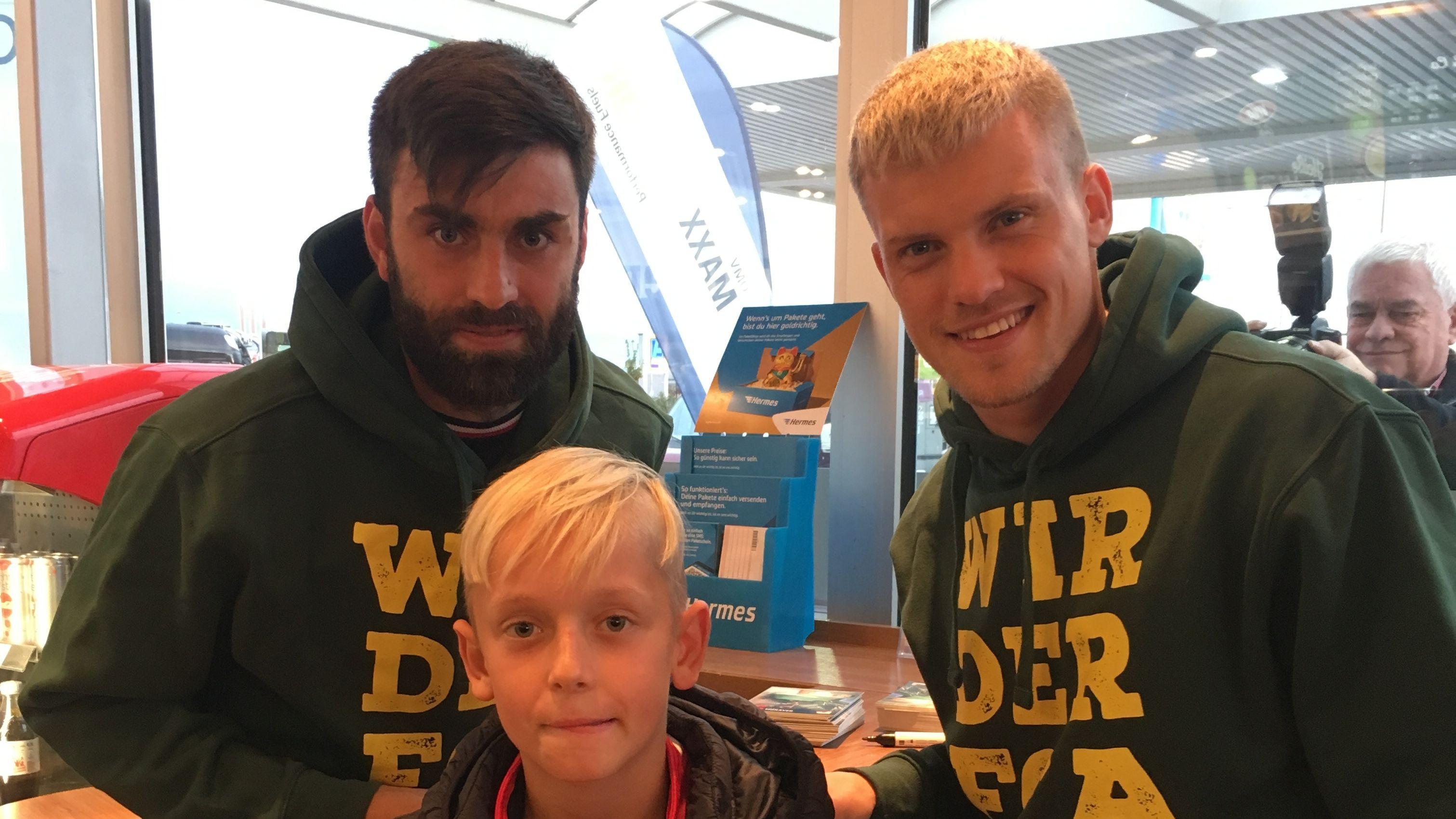 FCA-Spieler Jan Morawek und Philipp Max mit einem jungen Fan