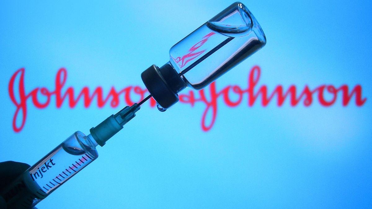 """Eine Impf-Spritze wird aufgezogen, im Hintergrund ist der Schriftzug """"Johnson & Johnson"""" zu lesen."""