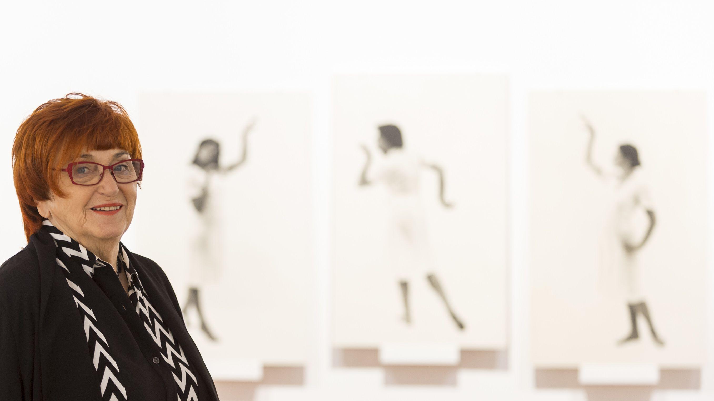 Die Künstlerin Valie Export steht mit roten Haaren und rot gerahmter Brille vor drei schwarz-weißen Fotografien bei einer Ausstellung 2019 in London