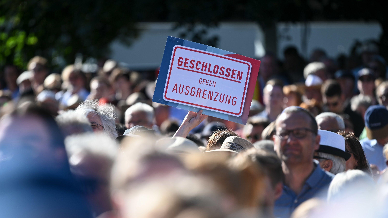 """""""Geschlossen gegen Ausgrenzung"""" steht auf einem Plakat auf der Kundgebung """"Zusammen sind wir stark"""" für Walter Lübcke am 27.06.2019 in Kassel."""