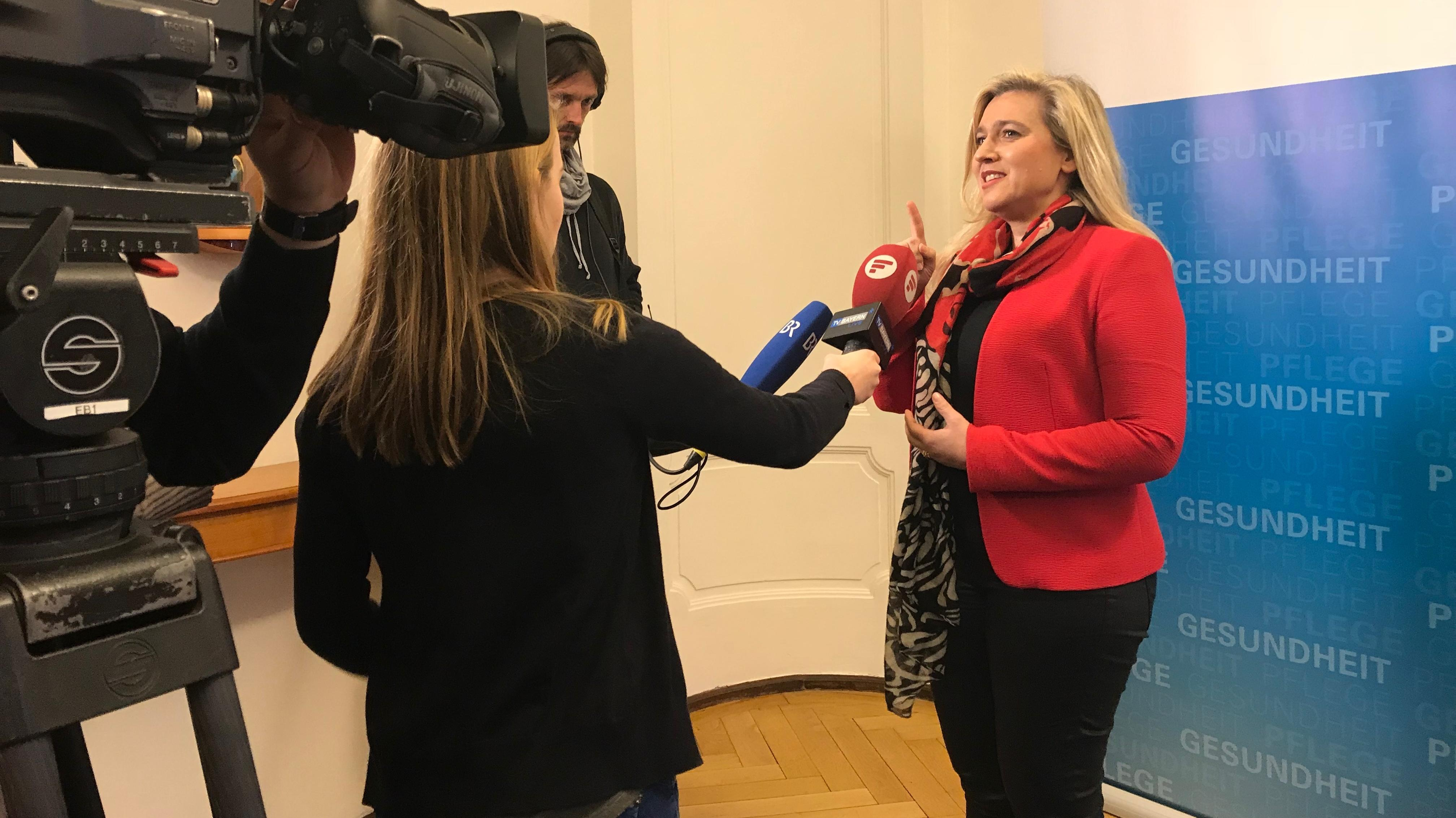 Gesundheistministerin Melanie Huml spricht in Mikrofone