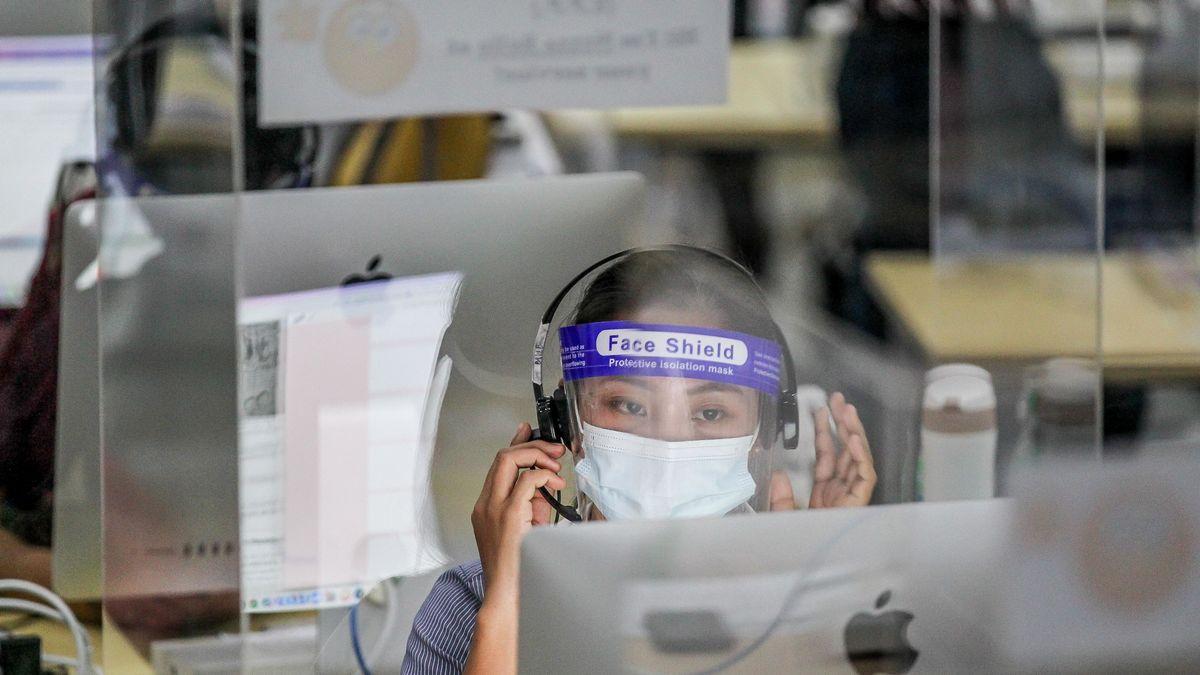Mitarbeiterin in einer Service-Hotline mit Face-Shield und Mundschutz