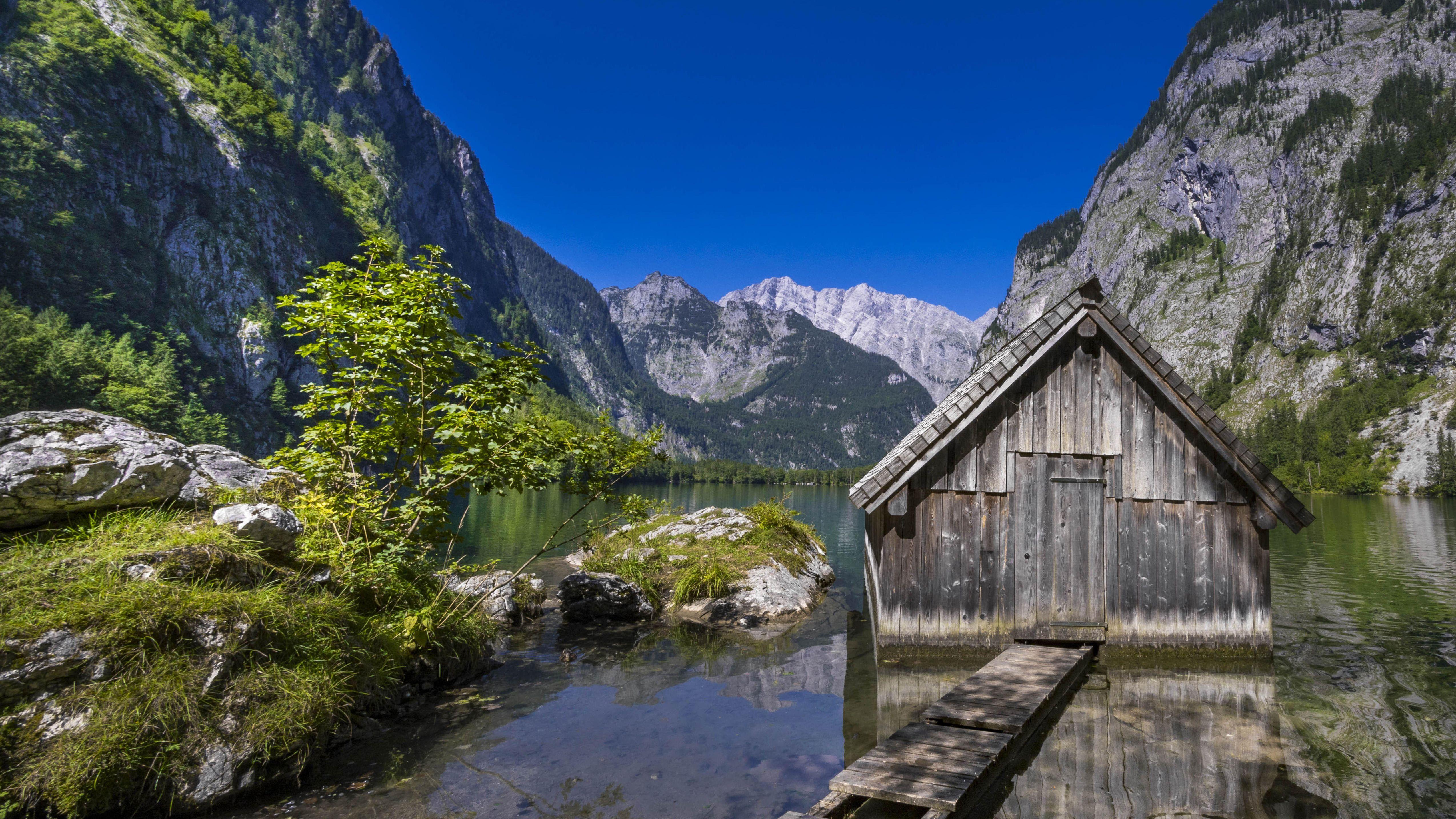 Der Obersee im bayerischen Nationalpark Berchtesgaden, dahinter das Watzmann-Massiv vor strahlend blauem Himmel
