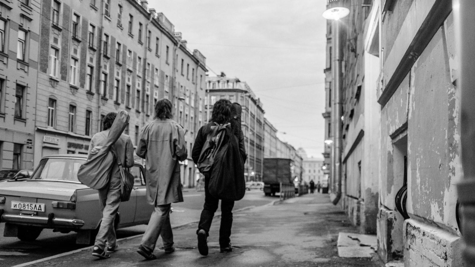 Zu sehen ist das Moskau der achtziger Jahre. Drei junge Männer gehen eine Straße entlang. Zwei von ihnen haben eine Gitarre auf dem Rücken hängen.