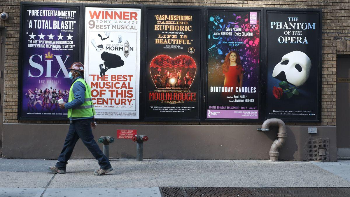 Passant vor Werbeplakaten für Musicals