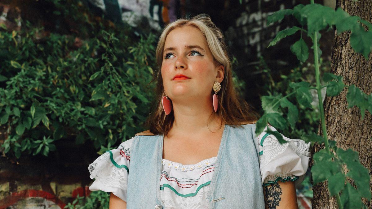 Katy J Pearson steht unter einem Baum und blickt nach oben.