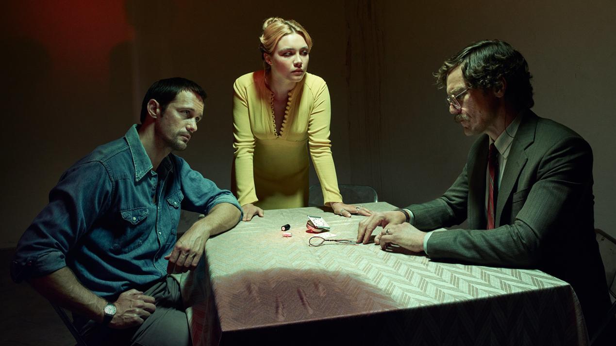 """Filmszene aus """"Die Libelle"""": zwei Männer sitzen sich an einem Tisch gegenüber, eine Frau steht mit aufgestützten Armen zwischen ihnen"""