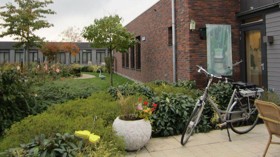 Ein Fahrrad steht im Demenzdorf in Hogeweyk (Niederlande) vor Wohngebäuden.
