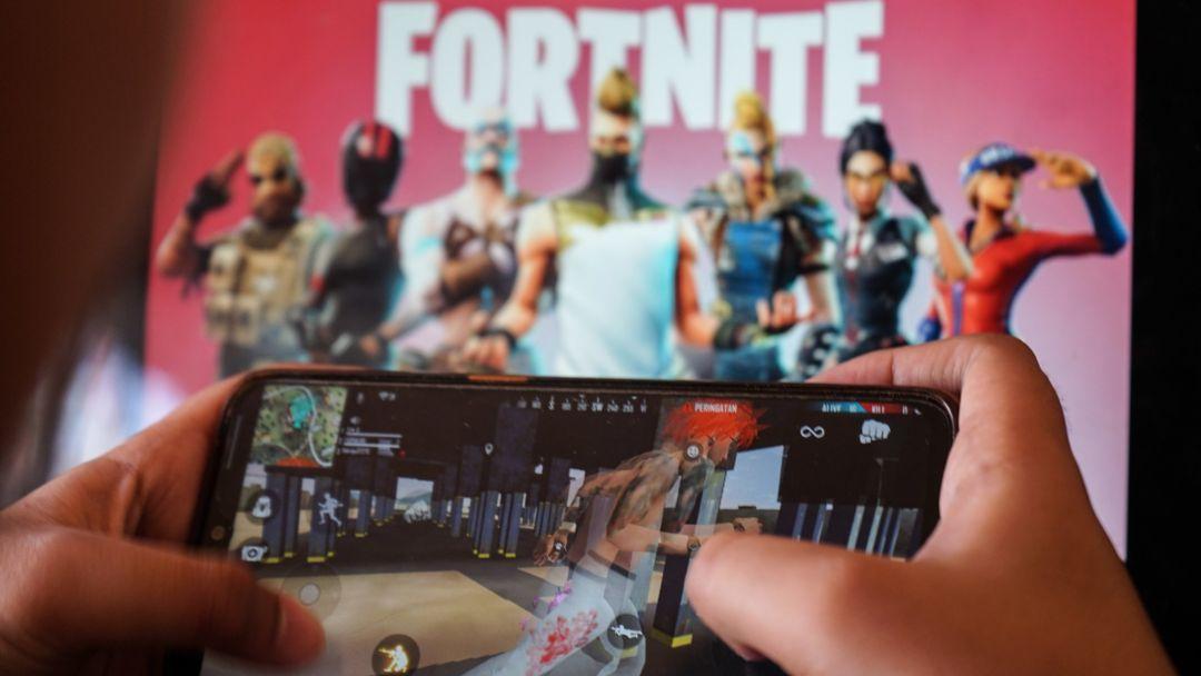 Ein Kind spielt ein Spiel auf einem Mobiltelefon mit einem Bild des Fortnite-Spiels auf dem Computerbildschirm im Hintergrund.