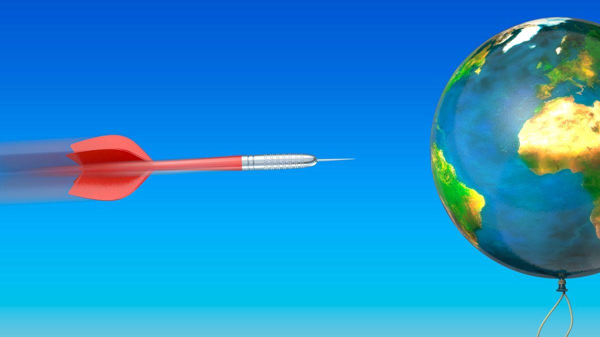 Ein Dartpfeil fliegt auf einen Luftballon zu auf den die Weltkarte gemalt ist.