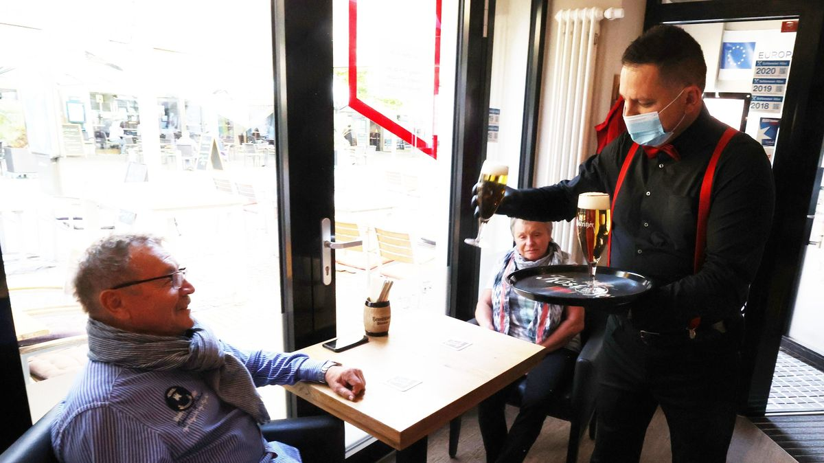 Ein Kellner mit Mundschutz serviert zwei Gästen im Restaurant Bier.