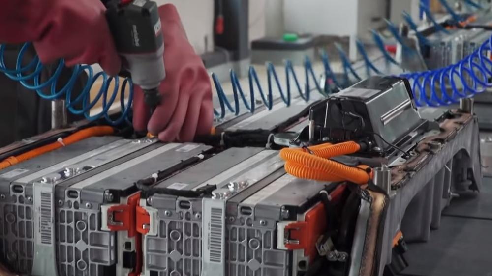 In einer Recyclinganlage wird der Batterieblock eines Elektrofahrzeugs von Hand geöffnet.