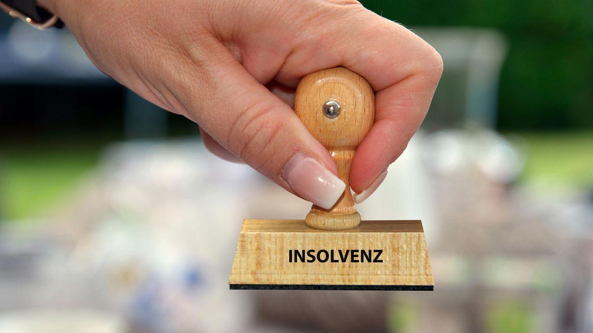Symbolbild: eine Frauenhand hält einen Stempel mit der Aufschrift Insolvenz