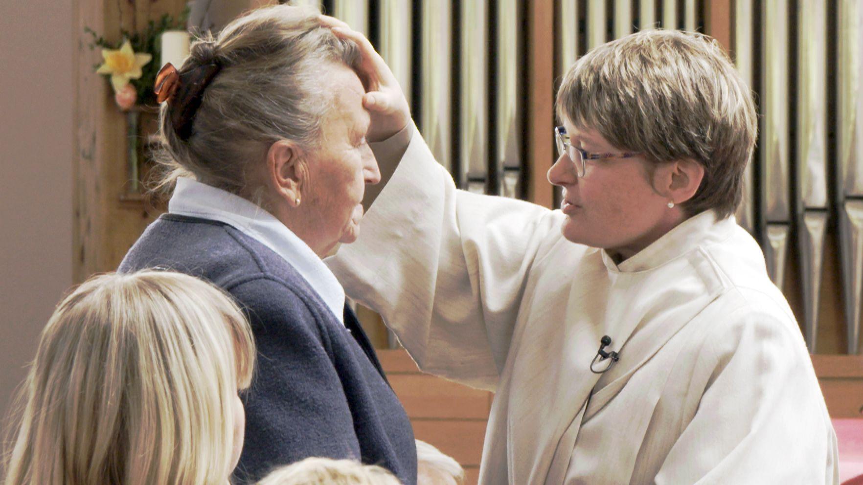 Theologin Maria Kotulek segnet eine Besucherin des Demenz-Gottesdienstes in Rosenheim