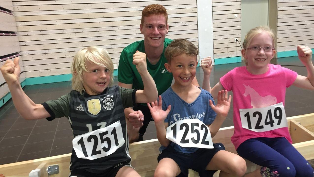 Drei Kinder und ein Trainer in einer Bayreuther Sporthalle.