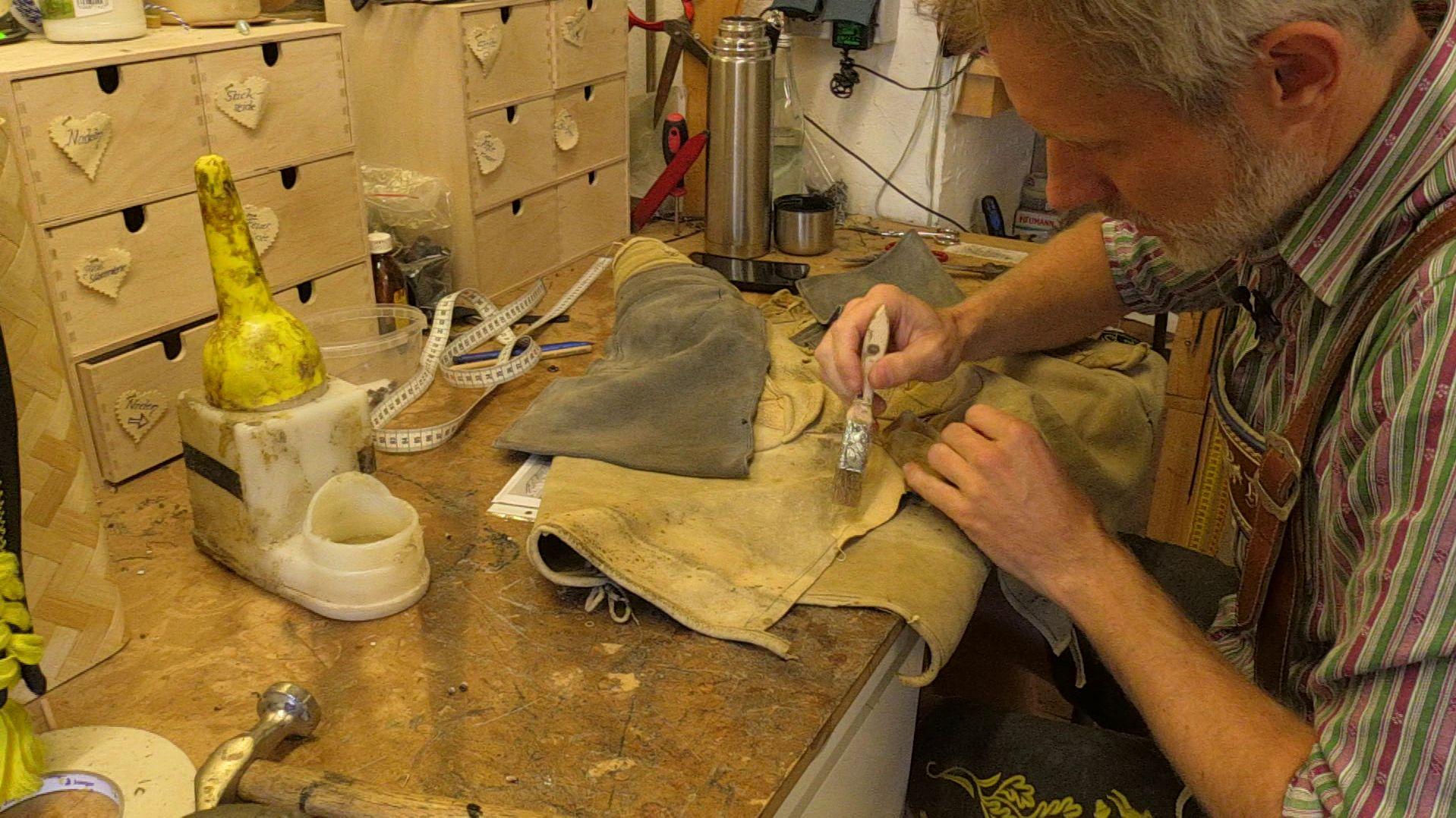 Lederhosenexperte Michael Auer beim Reparieren einer Lederhose.