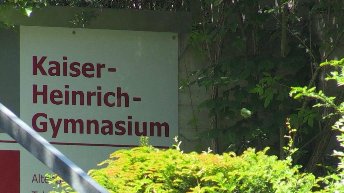 """Auf einem Schild steht in großen, roten Buchstaben """"Kaiser-Heinrich-Gymnasium"""" neben dem Eingang zur Schule."""