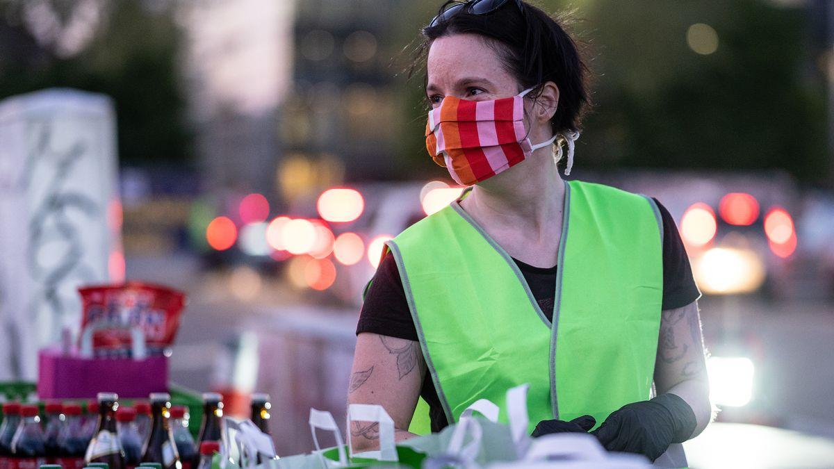 Frau mit Mundschutz verteilt Essenstüten und Getränke