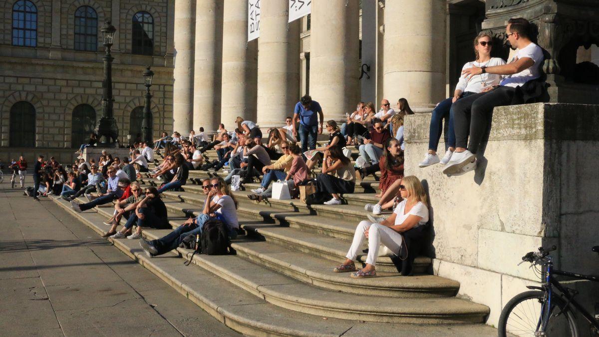 Passanten sitzen auf den Treppen vor dem Eingang der Staatsoper in der Sonne